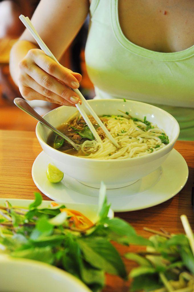 Vietnamsko jed Pho se je s palčkami (za rezance) in žlico (za tekoči del juhe)